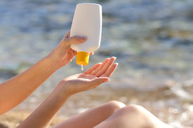 image of body-lotion  - Woman hands putting sunscreen from a bottle on the beach with the sea in the background - JPG