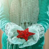 Female hands in light teal knitted mittens with entwined red star. Winter and Christmas concept.