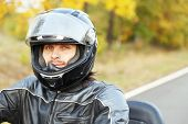 Biker man in black helmet sits on bike