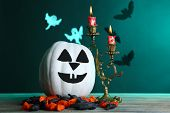 White Halloween pumpkin and candles on wooden table on dark color background