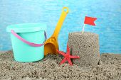 Sandcastle with flag and plastic bucket, spade on sandy beach