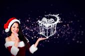 Pretty girl presenting in santa outfit against glowing christmas gift