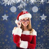 Sexy santa girl wearing spectacles against blue vignette