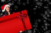 Woman holding a card with red christmas ribbon on black background