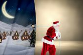 Santa claus pulling rope against grey room