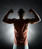 sport, bodybuilding, strength and people concept - young man showing biceps over black background from back