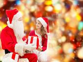 holidays, christmas, childhood and people concept - smiling little girl with santa claus and gifts over red lights background