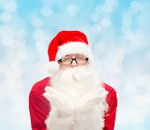 christmas, holidays and people concept - man in costume of santa claus blowing on palms over blue lights background