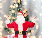 christmas, holidays and people concept - man in costume of santa claus with raised hands over tree lights background
