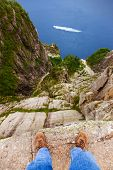 Man standing on cliff Preikestolen in fjord Lysefjord - Norway - nature and travel background