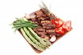 fresh grilled meat beef ribs with asparagus thyme and tomatoes on wooden plate isolated over white background