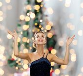 people, happiness, holidays and glamour concept - smiling woman raising hands and looking up over christmas tree lights background