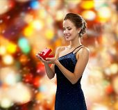 winter holidays, christmas, presents, luxury and people concept - smiling woman in dress holding red gift box over red lights background