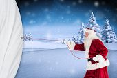 Santa pulls something with a rope against snowy landscape with fir trees