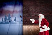 Santa pulls something with a rope against room with brick wall
