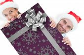 Festive young couple smiling at camera against christmas wrapping paper with bow