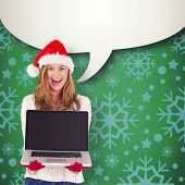Festive blonde showing a laptop against green vignette