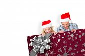 Young festive couple against christmas wrapping paper with bow
