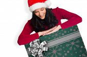Woman smiling while looking down against christmas wrapping paper with bow