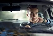 Fashionable young attractive man driving his car