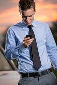concentrated young businessman looking ta smart   phone