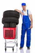 young mechanic with full shopping carts of new  tires car