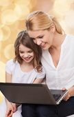 family, childhood, holidays, technology and people concept - smiling mother and little girl with laptop computer over beige lights background