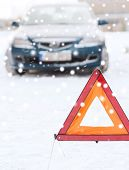 transportation, winter and vehicle concept - closeup of warning triangle and car
