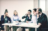 business, technology and office concept - serious business team with smartphones making calls in office