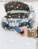 transportation, winter, people and vehicle concept - closeup of man with broken car and cell phone