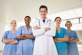 image of nurse practitioner  - Smiling doctor and nurses with arms crossed wearing breast cancer awareness ribbon - JPG