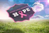 Breast cancer awareness badge against sunny landscape
