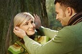 Caucasian boyfriend caressing happy romantic blond lady leaning against tree at forest, outdoor. Smiling.