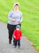 Overweight woman with her son running together.