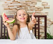Little smiling girl with watermelon at light room