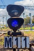 Traffic light shows blue signal on railway.