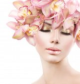 Fashion Beauty Model Girl with Orchid Flowers Hair. Spa woman. Bride. Perfect Creative Make up and Hair Style. Hairstyle. Nude makeup. Bouquet of Beautiful Flowers on lady's head