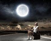 Young girl traveler sitting on bag at night