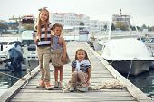 Group of 3 fashion girls wearing navy clothes in marine style walking in the sea port