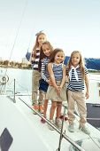 Group of fashion kids wearing navy clothes in marine style posing on white yacht in sea port