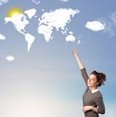 Young casual girl looking at world clouds and sun on blue sky