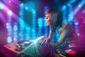 Pretty Dj mixing music in a club with blue and purple lights