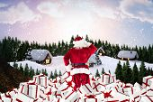 Santa standing on pile of gifts against cute village in the snow
