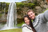 Iceland couple selfie wearing Icelandic sweaters by Seljalandsfoss waterfall on Ring Road in beautiful nature landscape on Iceland. Woman and man model in typical Icelandic sweater. Multiracial couple