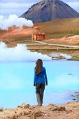 Iceland hot spring geothermal energy power plant in Namafjall in Lake Myvatn area. Woman tourist enjoying Icelandic nature landscape on Route 1 Ring Road.