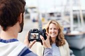Man taking pictures of girlfriend on holiday travel vacation tourist couple