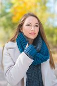Gorgeous young woman in stylish fall or autumn fashion standing in a white coat and blue knitted ensemble smiling at the camera in a park
