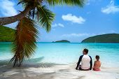 Back view of father and daughter enjoying beach vacation at Caribbean