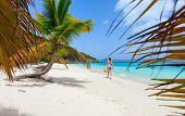 Back view of a young beautiful woman walking along white sand tropical beach