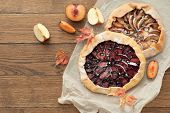 homemade sea biscuit with apples, plums, raisins, blueberries and cinnamon on wooden background. Autumn still life.